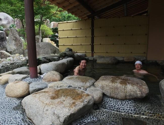 岩を積んだ庭に面した露天風呂