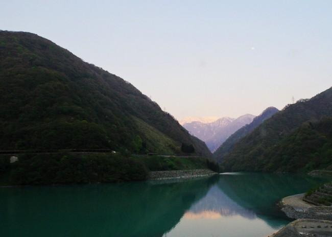 夕闇迫る宇奈月湖の向こうには雪を抱いた黒部の渓谷が、左手にはトロッコ電車の軌道が見える