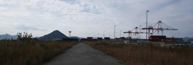 コンテナヤードの空き地の先には似島にある安芸の小富士が見える
