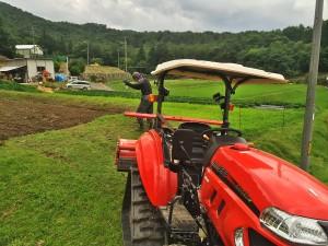 トラクターで農作業中
